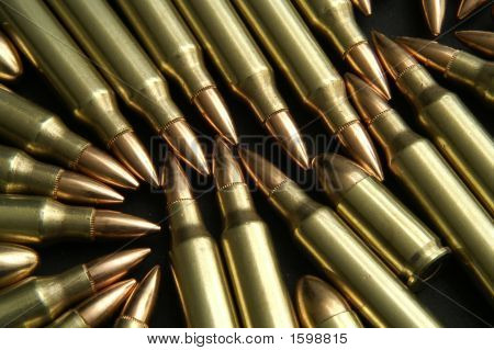 Rifle And Handgun Bullets On A Black Surface
