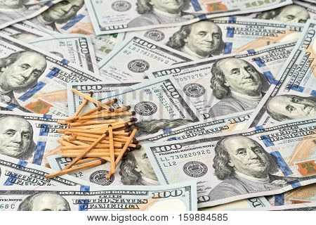 Pile of matches whole on the hundred-dollar bills, spread out as a background