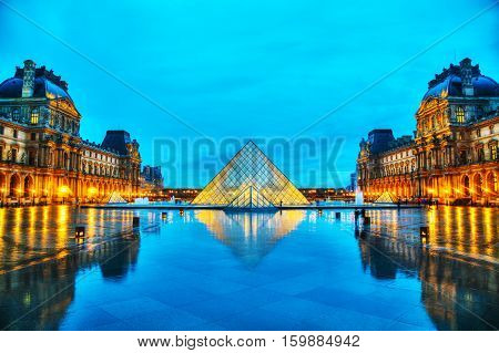 PARIS - NOVEMBER 4: The Louvre Pyramid on November 4 2016 in Paris France. It serves as the main entrance to the Louvre Museum. Completed in 1989 it has become a landmark of Paris.