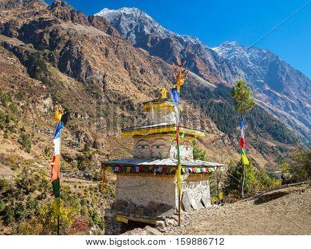 Stupa with Buddha wisdom eyes and prayer colorful flags in Hymalayas mountains. Manaslu region, Nepal