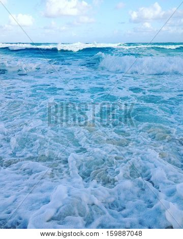 Blue and white ocean water waves with blue sky, clouds, sunshine and horizon background. Sea shore with sand, waves and sea foam.