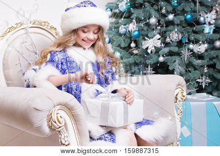 smiling little girl with gift box in a Christmas decorations and christmas thee background. The girl opening Christmas gift. Christmas time. Children's emotions of Santas' presents. Happy New Year