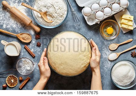 Hands working with dough preparation recipe bread, pizza or pie making ingridients, food flat lay on kitchen table background. Butter, milk, yeast, flour, eggs, sugar pastry or bakery cooking.