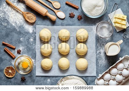 Buns dough homemade preparing recipe, ingridients food flat lay on kitchen table background. Working with butter, milk, yeast, flour, eggs, sugar pastry or bakery cooking.