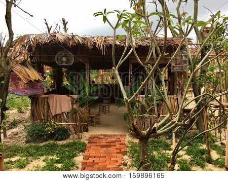 the original house with a thatched roof, sand floors, small chairs, hanging bird cages, next grow exotic plants