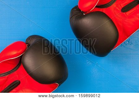Red and black boxing gloves on a blue wooden desk