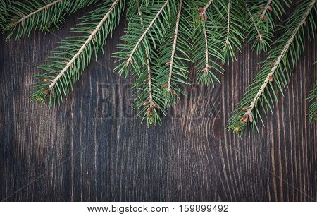 Christmas tree twigs of spruce arranged on aged wooden planks background holiday background in vintage style