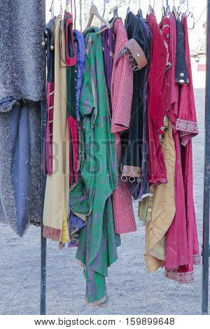 vertical view of a coat rack with some clothes and medieval dresses