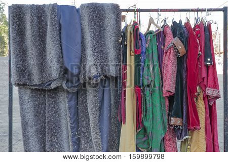 horizontal view of a coat rack with some clothes and medieval dresses