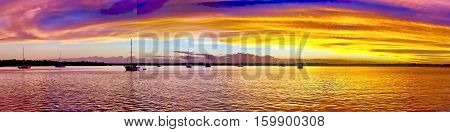 Grand Gold Dawn - Sunrise panorama over Inskip Point and Carlo Island with several yachts at anchor, highlighted in a golden glow and with vivid blue sky above.  Tin Can Bay, Queensland, Australia.