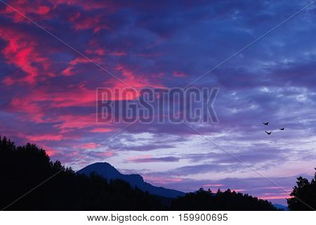 Picturesque view on European mountain ridges over dramatic sunset blue and violet sky with red clouds