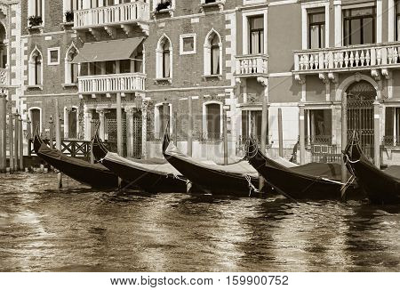 Row of docked venetian gondolas in black and white. Gondolas are very popular sort of entertainment in Venice Italy
