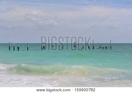A Caribbean beach with green water and blue skies.