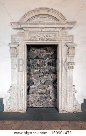 CATANIA ITALY - AUGUST 17 2016: Doorway blocked with lava stone in the 16th century Benedictine Monastery of San Nicolo l'Arena in Catania Sicily Italy