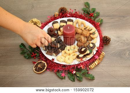 Detail photo of various homemade Christmas cookies special Czech sweets; x-mas decoration background with cookies on white plate with red candle with hand taking cookie on or from the plate