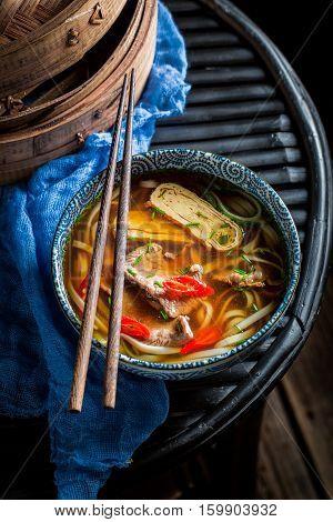 Tasty Thai Broth In Black Bowl With Chopsticks