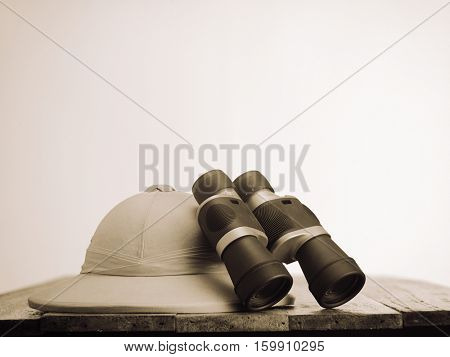 Old colonial hat  hat with a pair of  binoculars on wooden table