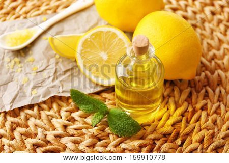 Beautiful spa composition with lemon essential oil on wicker mat, closeup