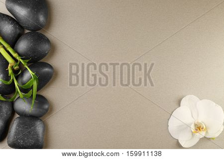 Spa stones, bamboo branch and orchid flower on color background