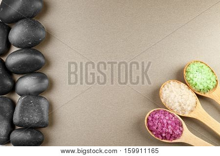 Spa stones and spoons with sea salt on color background