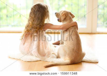 Little girl with golden Labrador dog in room