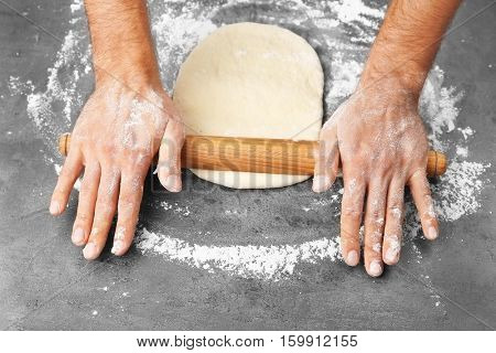 Male hands preparing dough for pizza on table closeup