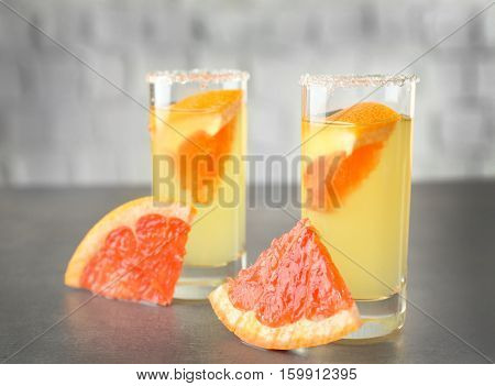 Colorful shot with grapefruit piece on gray table