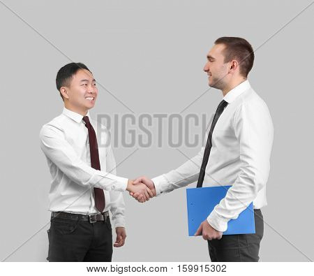 Handsome men shaking hands on light background