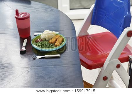 High chair at table with child's dinner, close-up