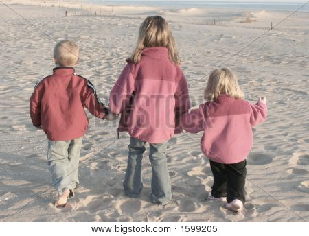 Three Kids Walking On Beach Together