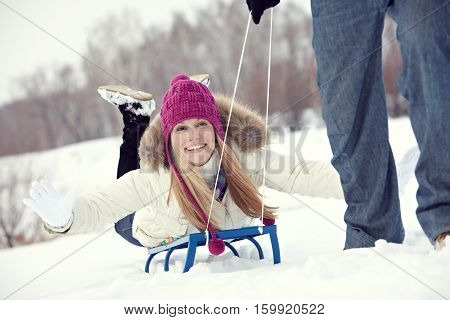 Young woman being ridden on a sled