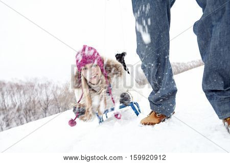 Young girl being ridden on sled by her boyfriend