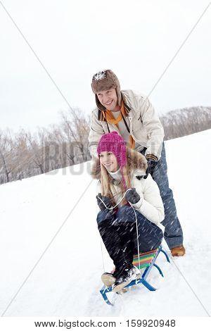 Man pushing his girlfriend on sled along field in winter