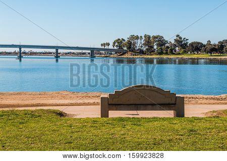 Cement bench at Vacation Isle Park on Mission Bay in San Diego, California with bridge in background.