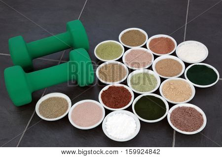 Body building supplement powder and dumbbell weights in porcelain bowls over slate background.