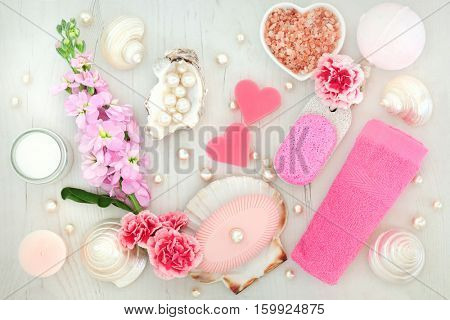 Spa and body scrub cleansing beauty products with flowers, himalayan salt, moisturising cream, soaps, pumice, flannel, bath bomb, pearls and shells.