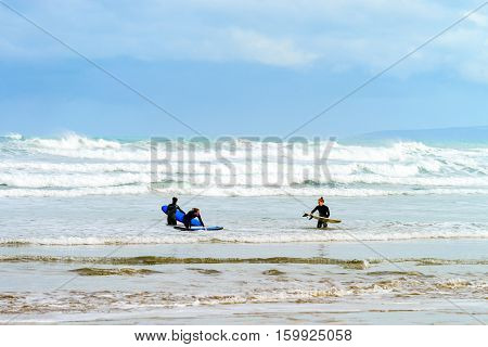 Adelaide Australia - August 14 2016: Female surfers with surfing boards entering the waters at Goolwa Beach
