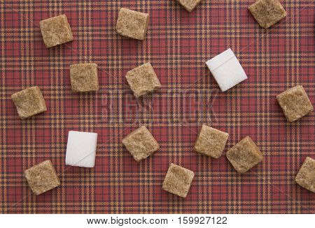 Brown and white sugar cubes on red squared background. Copy space. Top view
