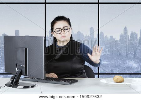 Portrait of fat businesswoman refuse potato on plate while sitting on the chair with winter background on the window
