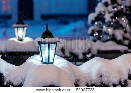 snowy street lamps lit in night city with fir-tree and christmas lights in background