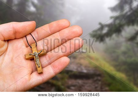 Female Hand With Cross On Haunted Forest Background