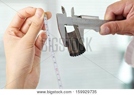 Female technician measuring mechanical part in maintenance shop