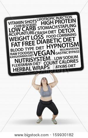 Picture of obese woman lifting diet methods on billboard while standing in studio isolated on white background