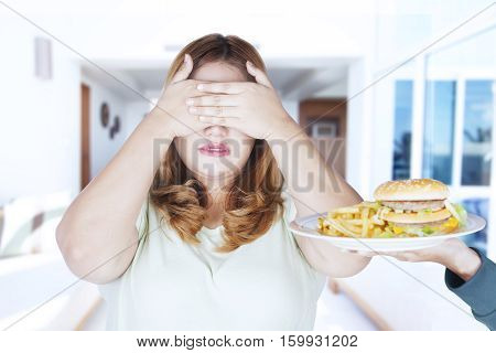 Blonde hair woman refusing hamburger and french fries with her eyes shot at home