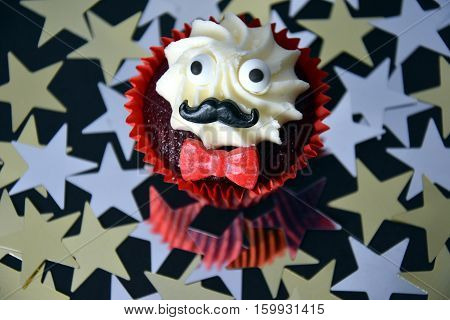 Cupcake with black mustache red bow tie and white cream on top. Movember cancer awareness in November month. Movember campaign against prostate cancer. Gold and silver stars in the background.