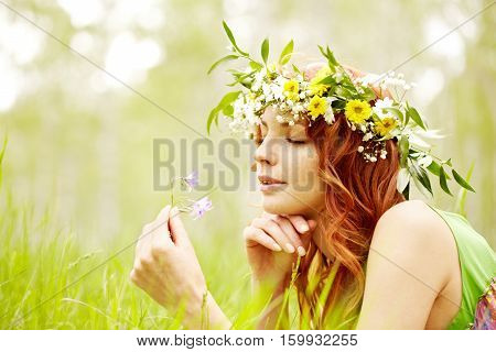 Portrait of a beautiful red-haired girl reclining on grass and smelling a wildflower