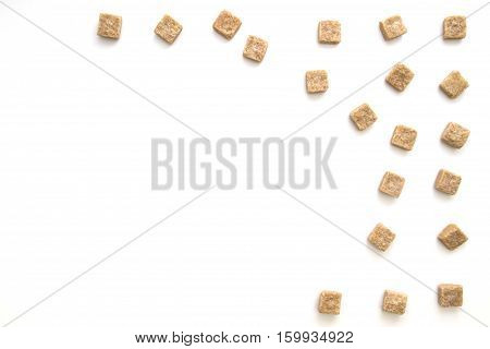 Brown sugar cubes on white background. Top view. Flat lay