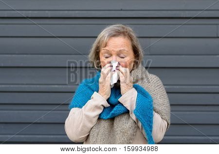Senior Woman Blowing Her Nose On A Tissue