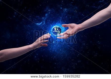 Male god hands about to touch the earth globe in the galaxy with bright shining stars and blue light illustration concept. Elements of this image furnished by NASA.