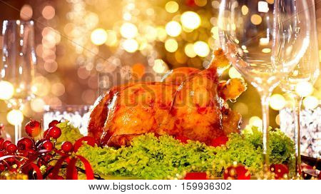 Christmas table setting with turkey. Christmas dinner. Holiday decorated table, Christmas tree, champagne and roasted turkey, New Year served table